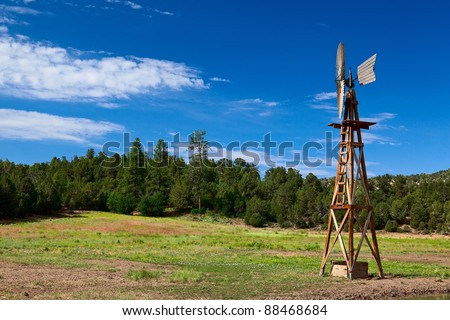 Old fashioned country windmill for pumping water - stock photo