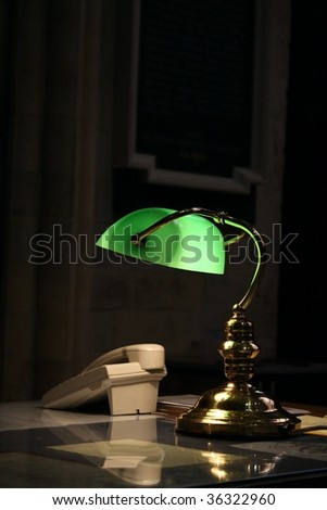 old fashioned desk lamp and telephone on a study table in a dark room