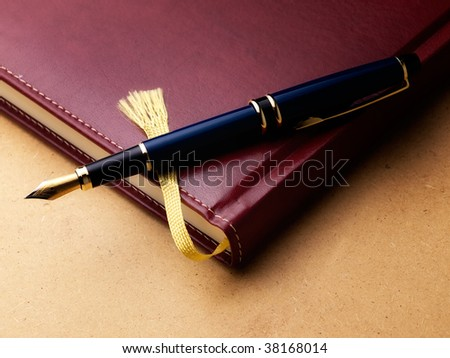 Old fashioned diary or log book with a fountain pen  on a grungy background. - stock photo