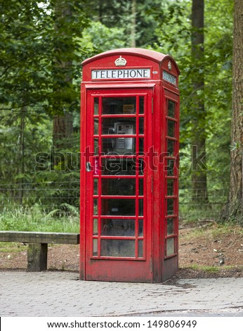 Old fashioned dusty and weathered british phone box in the forrest - stock photo