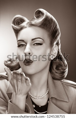 Old-fashioned Fascinating Pin-up Girl Blowing a Kiss. Retro Style. Heritage - stock photo