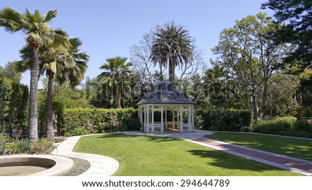 Old fashioned garden gazebo on manicured grass lawn - stock photo