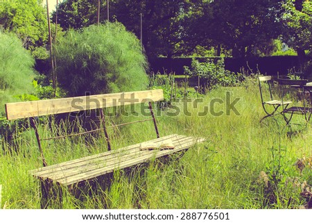 Old Fashioned Garden with Chairs, Table and a Book