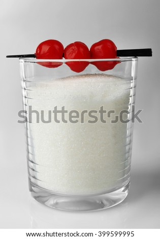 Old fashioned glass with granulated sugar and cocktail cherries on grey background - stock photo
