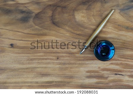 old fashioned ink dip pen for writing or drawing on wooden table with parchment paper background - stock photo