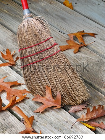 Old-fashioned jackstraw broom head  surrounded by oak leafs. - stock photo