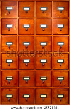 Old fashioned library card filing storage wood cabinet with drawers and index tab inserts on antique metal pulls - stock photo