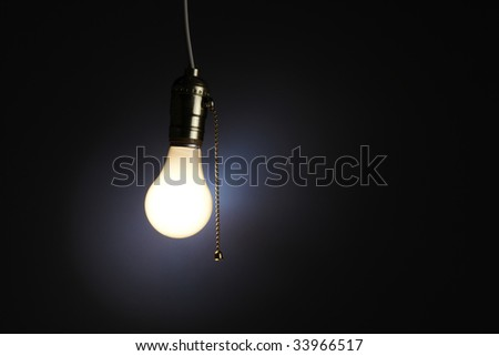 Old fashioned light bulb with pull chain - stock photo