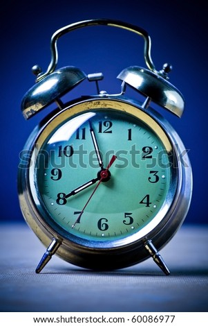 Old fashioned metal alarm clock on a blue background. - stock photo