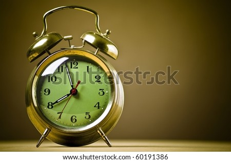 Old fashioned metal alarm clock on a brown background. - stock photo