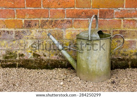Old fashioned metal watering can against a red brick wall