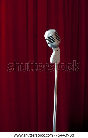 Old fashioned microphone on red curtain background - stock photo
