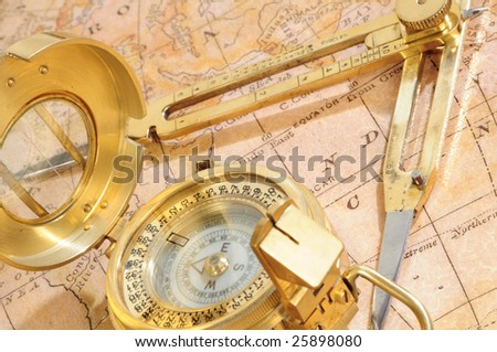old-fashioned navigation device on a background an old map - stock photo