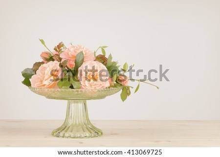 Old fashioned pink roses arranged in a green glass vase. Colors muted and vignette added  with photographic toning. - stock photo