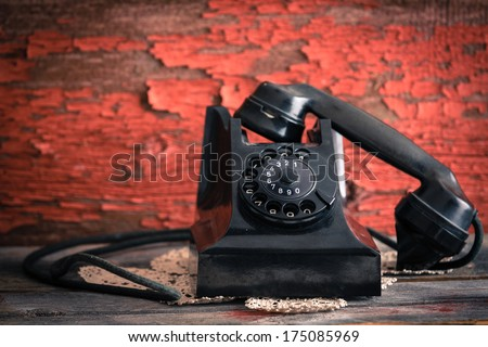 Old-fashioned rotary telephone with the handset off the hook effectively blocking the line against a rustic wall with distressed peeling red paint - stock photo
