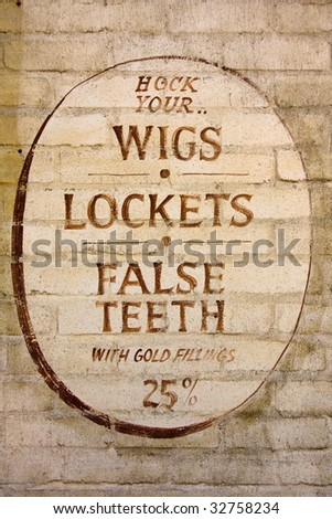 """Old fashioned sign inviting you to """"hock"""" your wigs, lockets and false teeth. - stock photo"""
