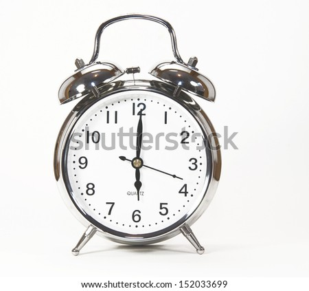 Old fashioned silver alarm clock against a white background