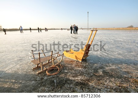 Old fashioned sledges on a frozen lake in the countryside from the Netherlands - stock photo