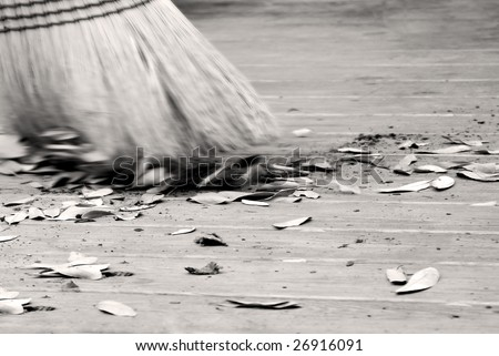 Old fashioned straw broom sweeping dirty ground with leaves and dirt flying - stock photo