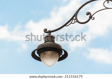 Old fashioned Street lamp against blue sky - stock photo