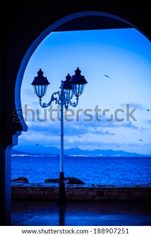 Old fashioned street lamp against the ocean - stock photo