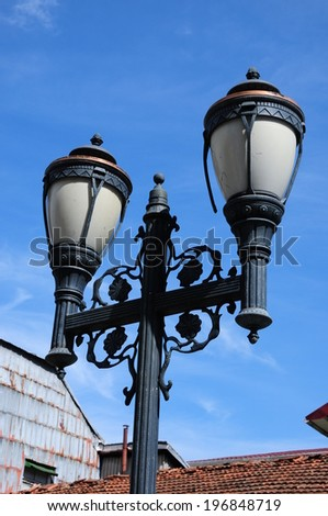 Old fashioned street lamp on blue sky - stock photo