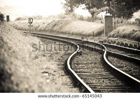 old fashioned styled rail tracks merging into one - stock photo