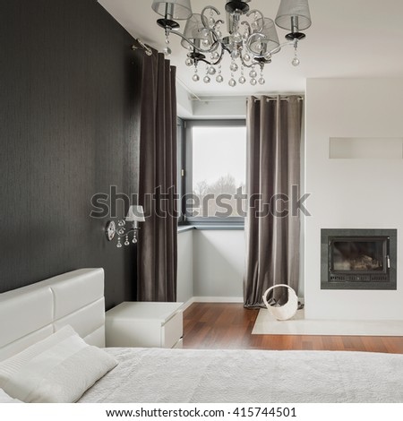 Old fashioned stylish bedroom with fireplace - stock photo