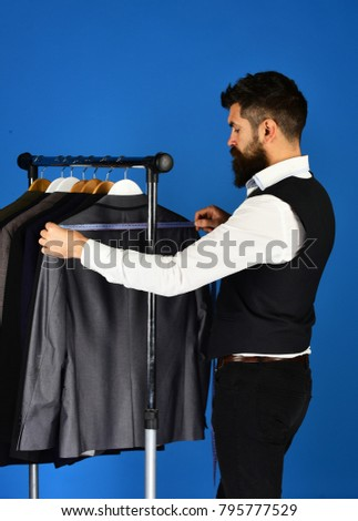 Old fashioned tailor measuring model in small atelier studio on blue background to make classic suit with jacket. Tailoring and fashion concept