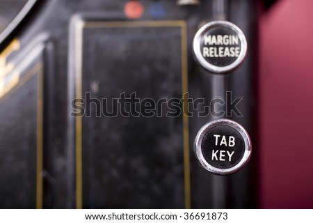 Old fashioned typewriter with the Tab key in sharp focus and the margin release key behind. - stock photo