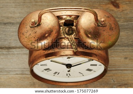 old-fashioned vintage copper alarm clock on wooden background - stock photo