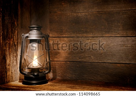 Old fashioned vintage kerosene oil lantern lamp burning with a soft glow light in an antique rustic country barn with aged wood wall and weathered wooden floor - stock photo