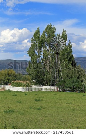Old fashioned windmill above a garden, Utah, USA. - stock photo