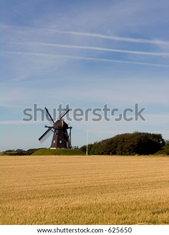Old fashioned windmill in landscape - stock photo