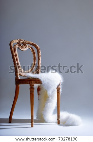 Old-fashioned wooden chair with white fur on it - stock photo