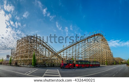 old fashioned wooden roller coaster blue sky red train - stock photo