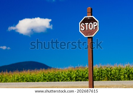 Old fashioned wooden stop sign against a blue sky, Stowe Vermont, USA - stock photo