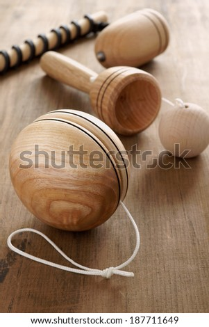 Old fashioned wooden toys.  Yo yo, cup and ball and a top and whip a retro childhood concept - stock photo
