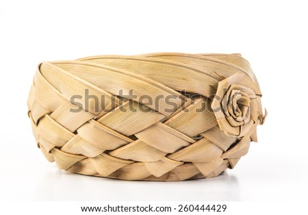 Old fashioned woven wicker basket weaved with thick bark strips with crafted flower decoration.  White background with copy space. - stock photo
