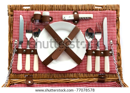 Old fasioned wicker picnic basket with cutlery - stock photo