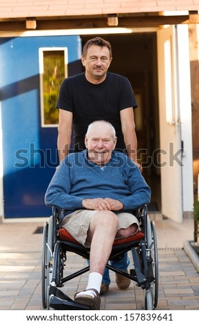 Old father being pushed in his wheelchair by his son.
