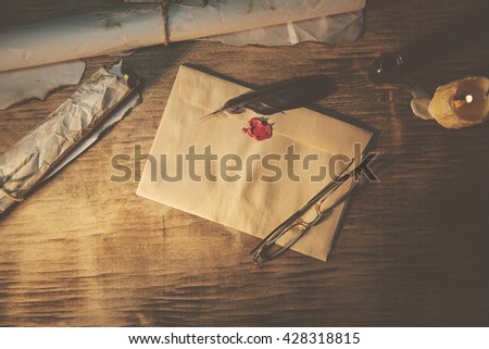 Old feather, envelope, sealing wax on wooden table - stock photo
