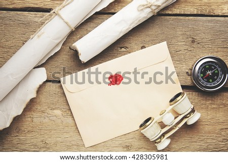 Old feather, envelope, telescope and compass on the wooden table - stock photo