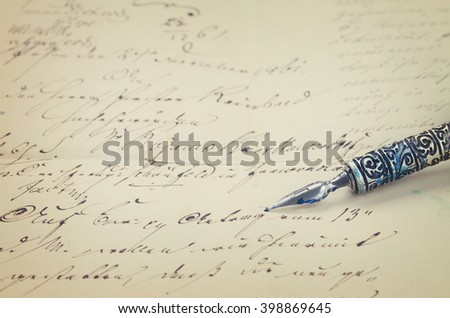 old  feather pen on  handwritten letter background, retro toned