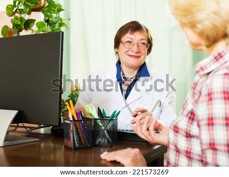 Old female doctor having good news for a patient