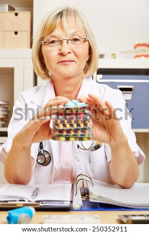 Old female doctor sitting with stack of many drugs in her office - stock photo