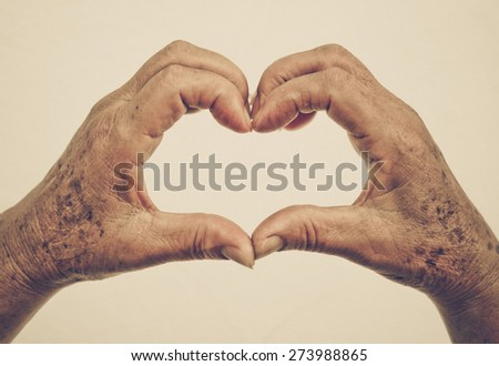 old female hands with freckles forming a heart shape - stock photo