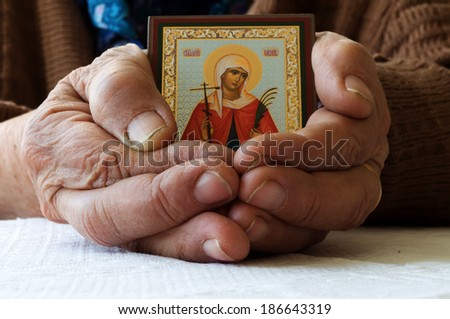 Old female hands with Orthodox icon - stock photo
