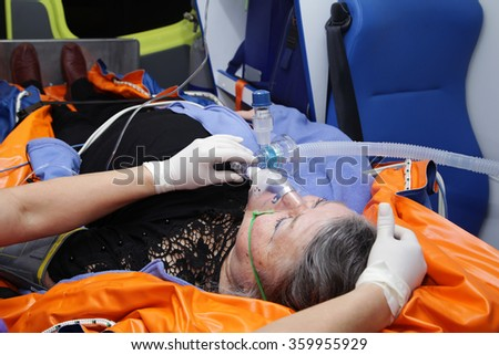 Old female lying on stretcher in the ambulance with oxygen mask on face - stock photo