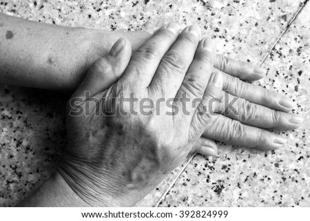 Old female/woman hands on marble background. Black and white tone. - stock photo